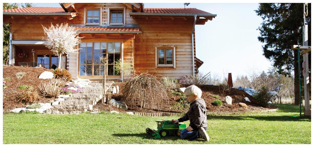 spielendes Kind vor dem Blockhaus von Moser Holzbau