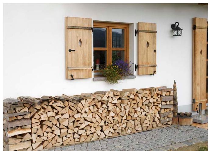 Holzstapel vor Blockhaus | Moser Holzbau